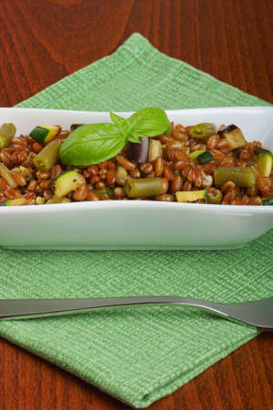 Spelt salad with eggplants, zucchini and green beans served in a white plate  Selective focus.