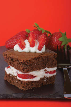 Fancy strawberry brownie with whipped cream  Strawberries are out of focus in the background