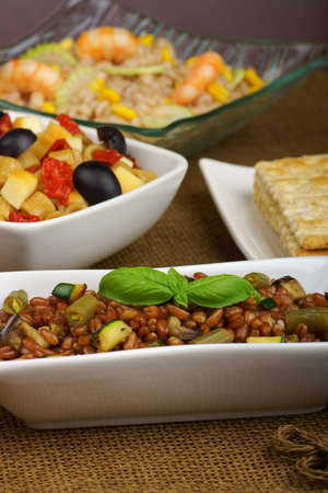 Spelt salad with eggplant, zucchini and green bean served in a white plate  Summer pasta salad and pearl barley salad out of focus int he background  Selective focus, shallow DOF