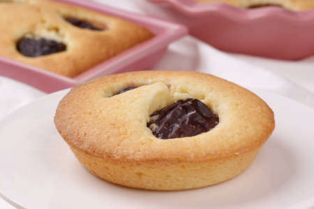 Small plum cake on a white cake stand  Plum cakes in pink pottery cake tins out of focus in the background