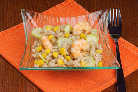 Pearl barley salad with shrimps, corn and celery served in a glass plate  Stock Photo