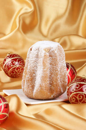 Christmas composition with Pandoro, the typical italian Christmas cake  Golden background with copy space