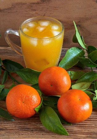 The mandarins and tangerine juice on a wooden background