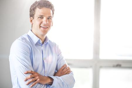 Portrait of businessman standing arms crossed in office Reklamní fotografie