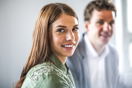 Portrait of beautiful businesswoman with male colleague in background