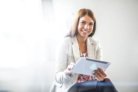 Portrait of smiling young businesswoman using digital tablet in office