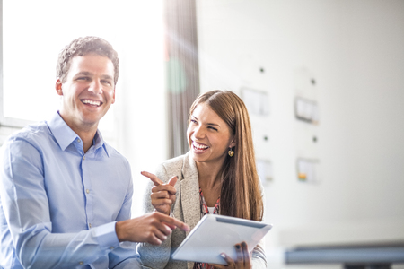 Portrait of cheerful businessman with female colleague using digital tablet in office