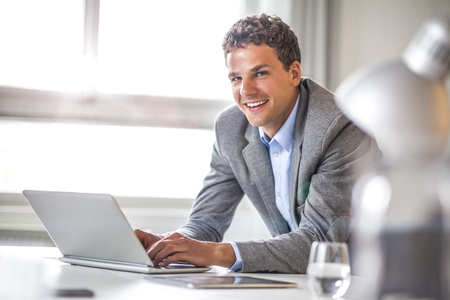 Portrait of smiling young businessman using laptop in office Stock Photo