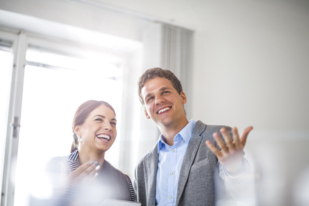 Cheerful young business people looking away in office Reklamní fotografie