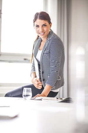 Portrait of smiling young businesswoman holding digital tablet while sitting on desk in office