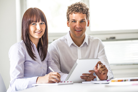 Portrait of young business people using digital tablet in office