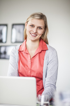 Portrait of happy young businesswoman using laptop in creative office Stock Photo