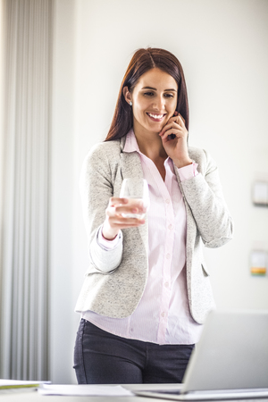 Smiling young businesswoman holding glass of water in office