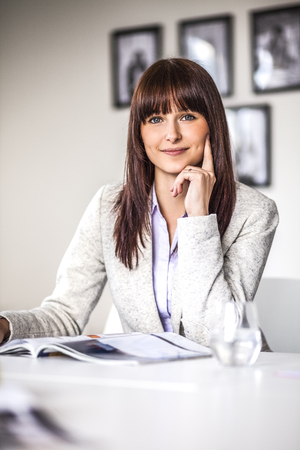 Portrait of happy young businesswoman with brochure in creative office