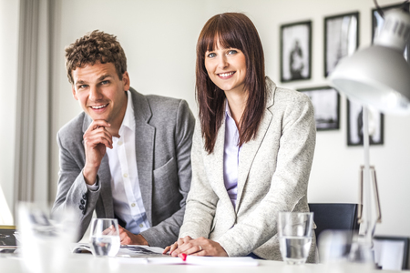 Portrait of young business people at table in office