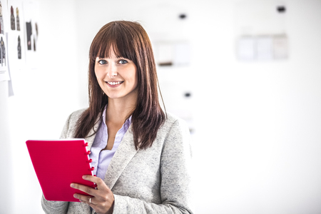 Portrait of happy young businesswoman writing in diary at office