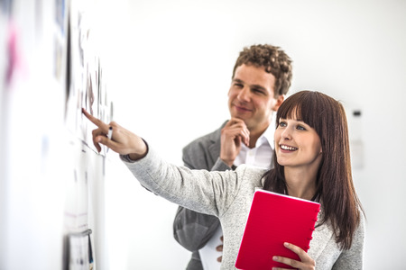 Jonge onderneemster met mannelijke collega-brainstorming aan boord in bureau