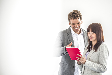 Smiling young business people discussing over note pad in office