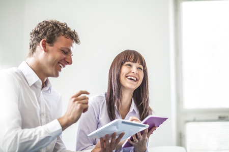 Cheerful young business people discussing together in office