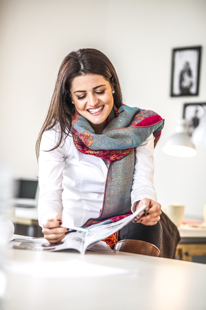 Smiling young businesswoman analyzing brochure in creative office