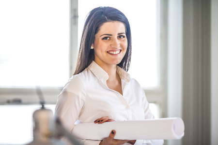 Portrait of young businesswoman holding blueprint in office