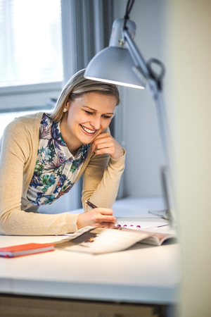 Smiling businesswoman writing notes by lit lamp in office