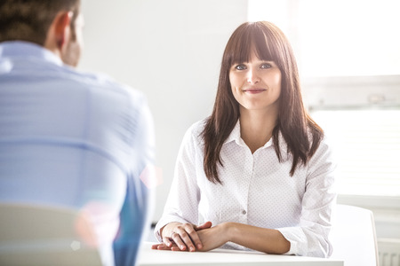 Portrait of confident young businesswoman with male colleague in office