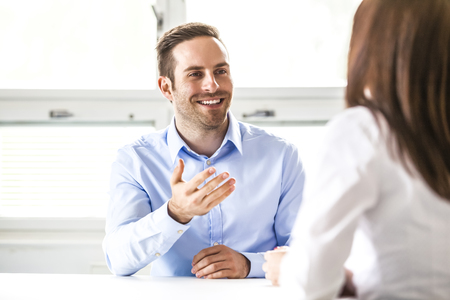 Young businessman discussing with female colleague in office