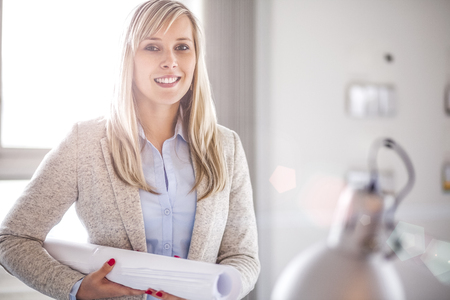 Portrait of confident young female architect holding rolled up blueprint in office