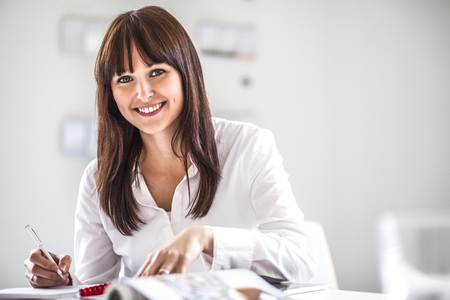 Portrait of smiling young businesswoman working at desk in office Reklamní fotografie