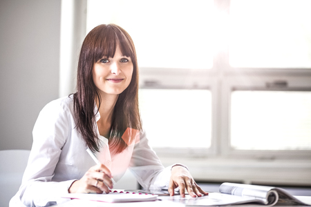 Portrait of beautiful young businesswoman working at desk in office