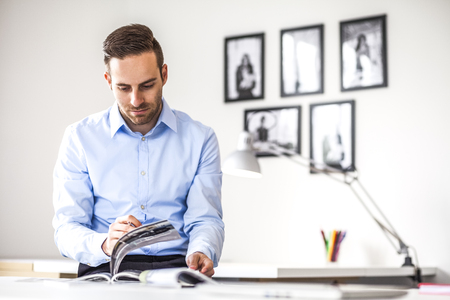Young businessman analyzing brochures at desk in office