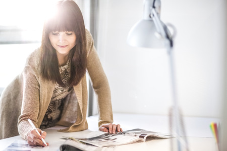 Young businesswoman analyzing brochures at table in office