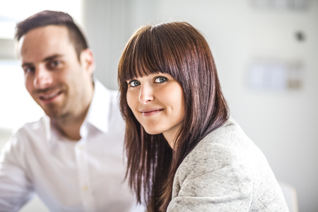 Portrait of beautiful young businesswoman with male colleague in office