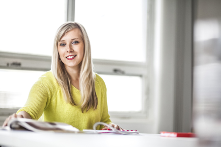 Portrait of beautiful young businesswoman working at table in office