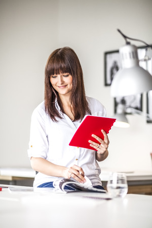 Young businesswoman with diary analyzing brochure at office desk
