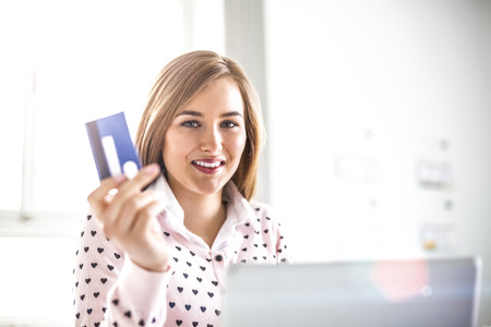 Portrait of smiling young businesswoman shopping online in office