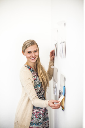 Portrait of smiling young businesswoman sticking notes on wall in creative office