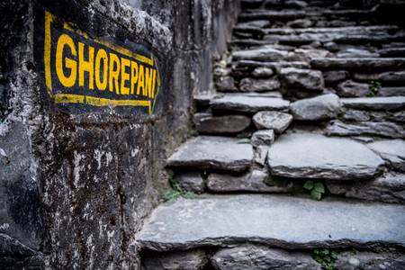 Nepal, March 2017: A sign indicates the way to Ghorepani at Birethanthi, the start of the Annapurna circuit trek in the Annapurna region, Nepal.