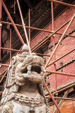 2015 년 지진으로 손상된 많은 구조물 중 하나를 지탱하기 위해 설치 한 비계가 화려한 조각상을 둘러 쌉니다. 더르 바르 광장, 카트만두. 스톡 콘텐츠