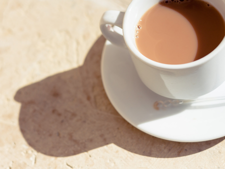 Tea with milk in a white cup in the morning sun with harsh shadows on a textured wood surface. Warm tones.