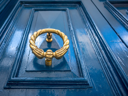 Antique gold or brass door knocker on a blue painted door. Old townhouse in Sliema, Malta.