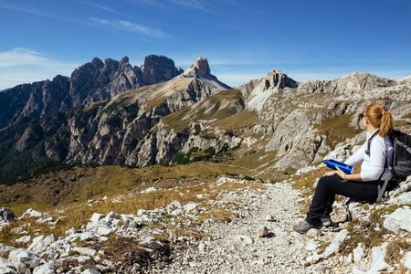 Woman looking into the distance at stunning mountain alpine scenery. Tre Cime natural park, Italian Dolomites