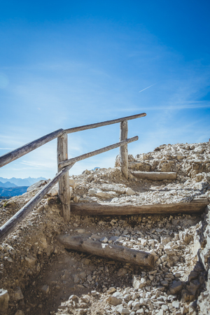 Stairs on an alpine trekking route seemingly leading to the heavens with vivid blue skies. Stock Photo