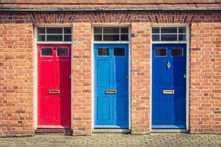 Three differently coloured front doors at the entrance of old English terraced houses. Canterbury, England. Reklamní fotografie