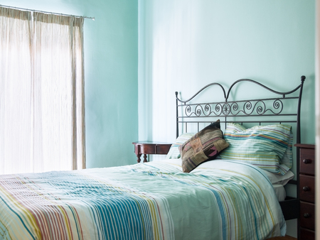 Bright and airy bedroom with rustic furniture and green  turquoise paint and soft furnishings from a bed and breakfast.