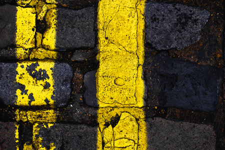 rule of thirds: Double yellow lines with cracked paint on a cobbled London street. vertical composition, rule of thirds.