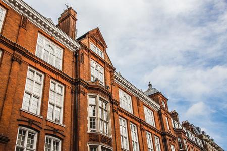 古い英語のれんが造りの家でロンドン、イギリス。斜めの線は、青い空と雲と組成。