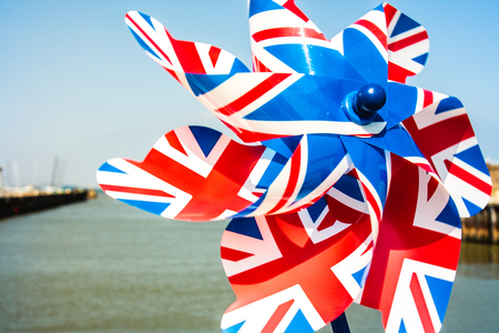 wind mill toy: colorful pinwheel with the union jack printed on it on a sunny day spinning in the wind.
