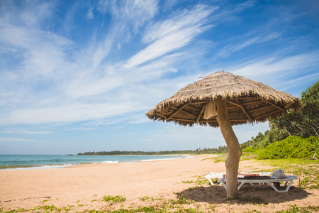 A straw umbrella and deckchair on kahandamodara beach, just outside of Tangalle, Sri Lanka.